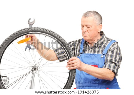 Mature bicycle mechanic looking at a wheel isolated on white background - stock photo