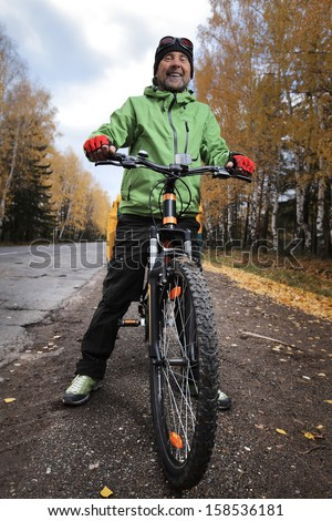 Mature bicycle tourist with loaded bike relaxing on an autumn road after riding - stock photo