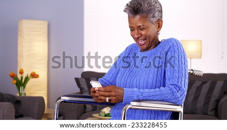 Mature black woman texting on smartphone