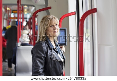 Mature Blond haired woman standing in the public transportation. people in the background. - stock photo