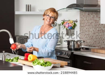 Mature blond woman cooking in new kitchen making healthy food with vegetables. Lifestyle image.