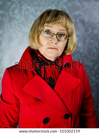 Mature blond woman in red coat - stock photo