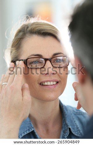 Mature blond woman with optician trying eyeglasses  - stock photo