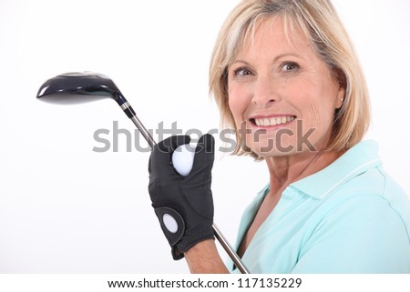 mature blonde woman taking golf club and golf ball - stock photo