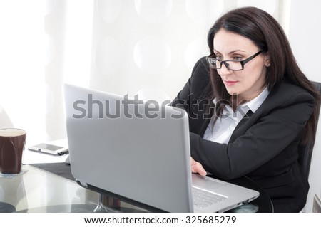 Mature brunette businesswoman is looking at the computer screen doing her paperwork, she is wearing a suit and glasses