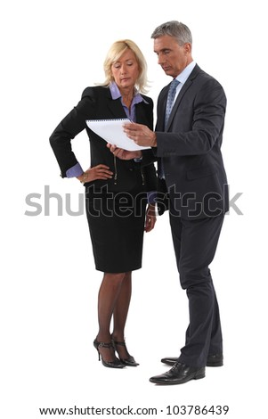 Mature business couple discussing a document - stock photo