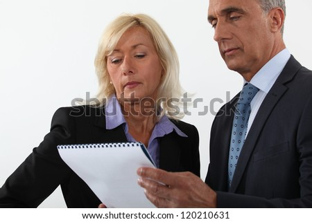 Mature business couple looking at a document - stock photo