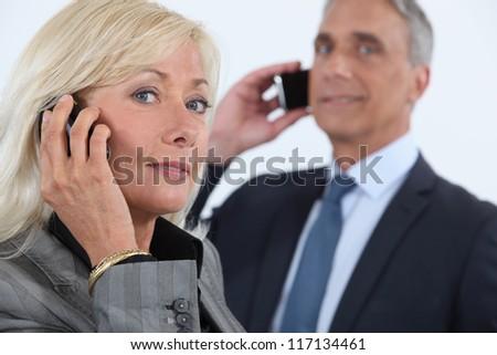 Mature business couple using cellphones - stock photo