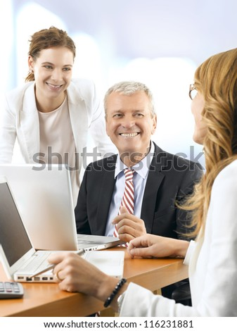 Mature business man discussing project with his colleagues. They working on laptop. - stock photo