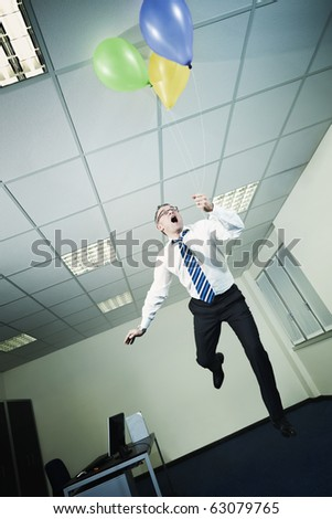 mature business man holding colored balloons and flying in office. Vertical shape, full length, Copy space - stock photo
