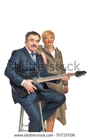 Mature business man in formal wear playing electronic guitar and being assisted by a woman isolated on white background - stock photo