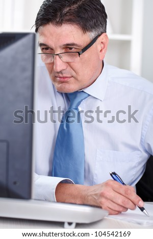 mature business man looking at computer screen and working - stock photo