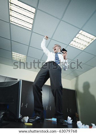 mature business man standing on desk and screaming for joy. Vertical shape, full length, copy space