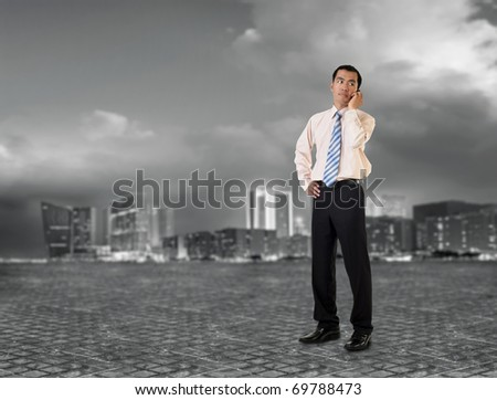 Mature business man talking on cellphone in modern city.