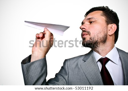 Mature business man throwing a paper plane - stock photo