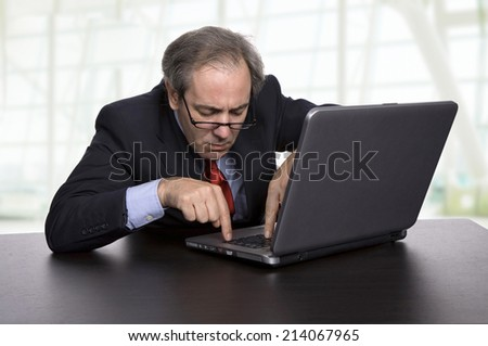 mature business man working with his laptop at the office - stock photo