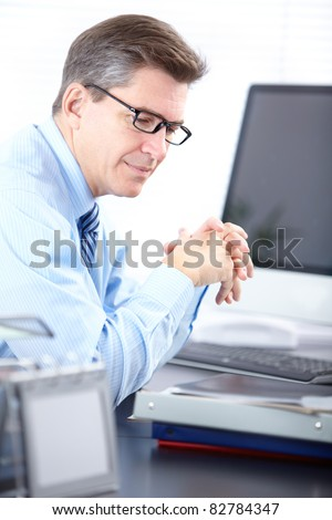 Mature business man working with papers in modern office. - stock photo