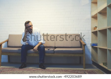 Mature business owner busy strategizing while sitting on sofa in small room. Male entrepreneur making hard Choice. Concept of decision in the life. Businessman thinking alongside copy space for text