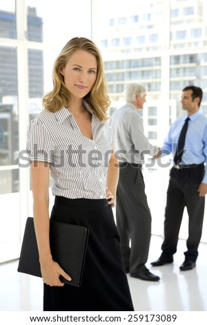 Mature Business Partners shaking hands in the background and young businesswoman looking at camera on foreground