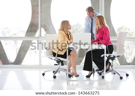 Mature business people discussing an idea around a laptop computer