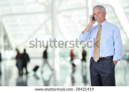 Mature Business Traveler Talking on Cell Phone in Airport Concourse with blurred travelers in background - stock photo