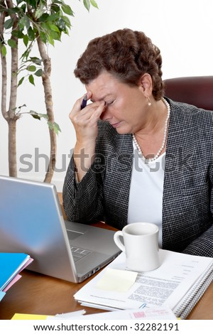 Mature business woman at her desk, eyes closed, worried about bills and financial problems - stock photo