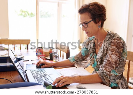 Mature business woman busy analyzing her business's financial statements for the past year - stock photo