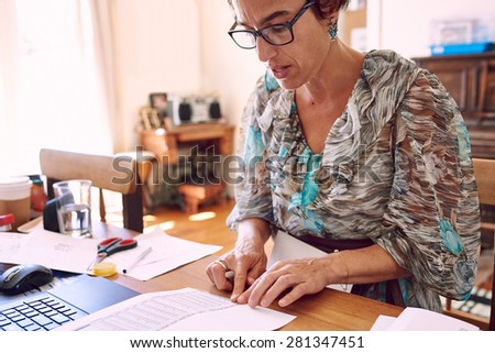 Mature business woman busy taping together pieces of paperwork to file her red tape in her home office as neatly as possible - stock photo