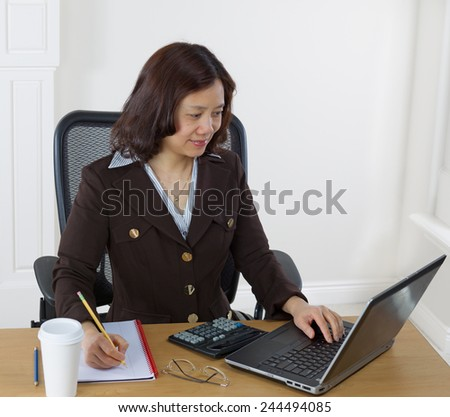 Mature business woman preparing to take notes while looking at the computer monitor.  Background is white walls.  - stock photo