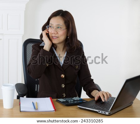 Mature business woman talking on cell phone while working with laptop, calculator and notepad on desktop. White wall background.  - stock photo