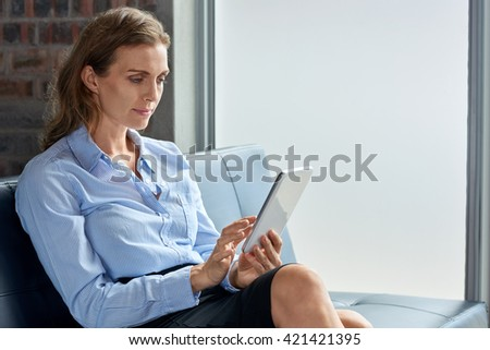 Mature business woman using digital tablet device in an office - stock photo