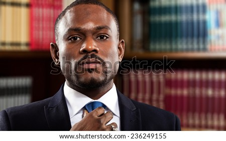 Mature businessman adjusting his tie - stock photo