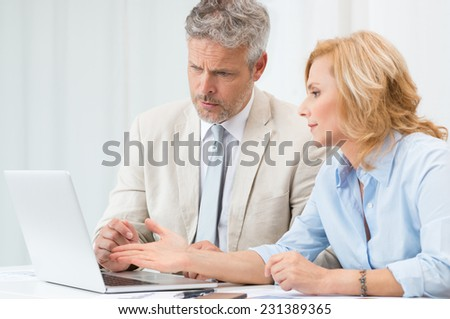 Mature Businessman And Businesswoman Discussing Data In Laptop At Office - stock photo