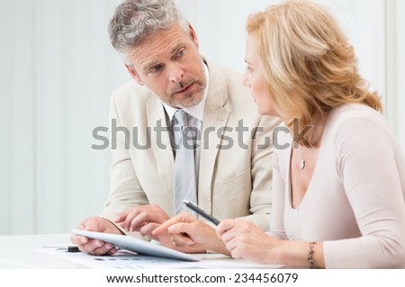 Mature Businessman And Businesswoman Discussing Data In Touchpad At Office - stock photo