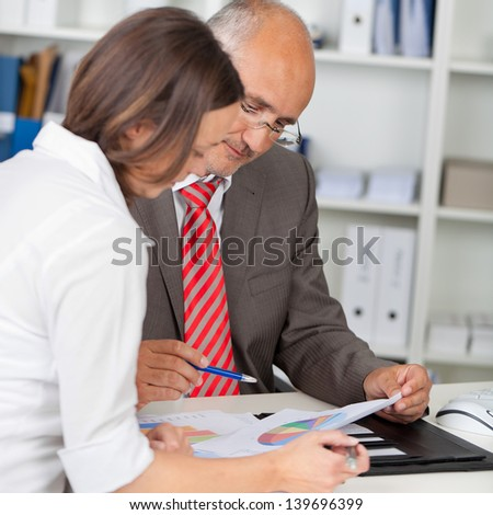 Mature businessman and businesswoman with graphs in meeting at office desk - stock photo