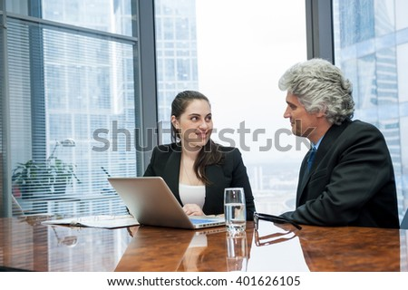 Mature businessman and young business woman discussing in a modern office - stock photo