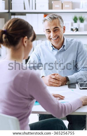 Mature businessman and young woman having a business meeting in the office, they are discussing together
