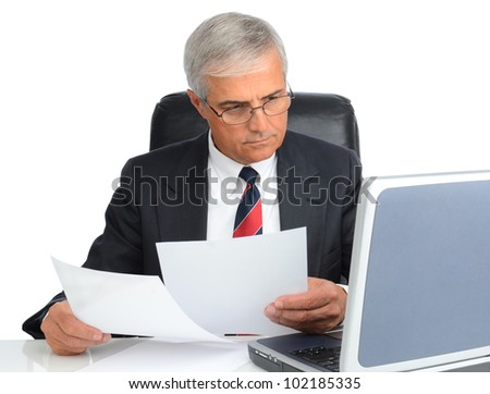 Mature businessman at desk comparing note to laptop screen. Man is wearing eye glasses over a white background. - stock photo