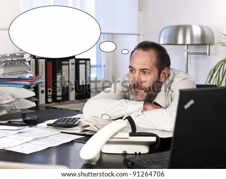 Mature businessman at desk with a thought bubble. Horizontal shot
