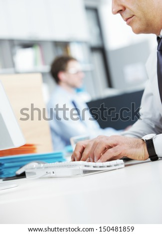 Mature businessman at desk working on computer - stock photo