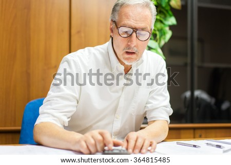 Mature businessman at work in his office - stock photo