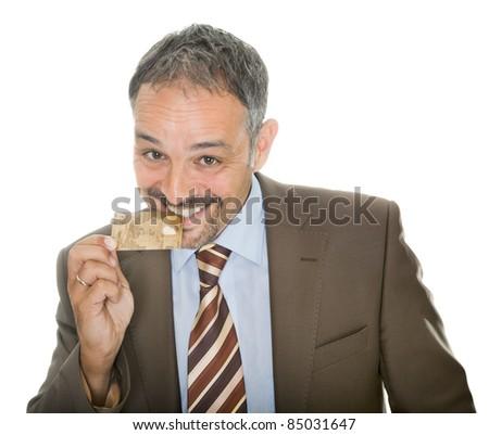 Mature businessman bites his credit card - stock photo