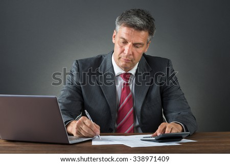 Mature businessman checking bills with calculator and laptop at desk against gray background