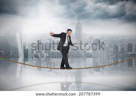 Mature businessman doing a balancing act on tightrope against room with large window looking on city - stock photo