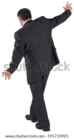Mature businessman doing a balancing act on white background