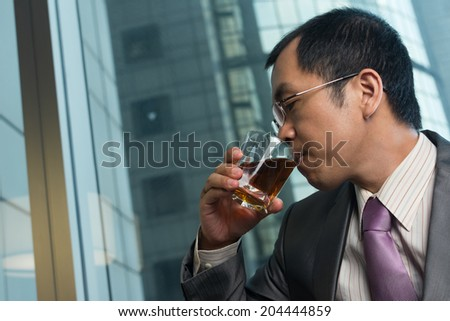 Mature businessman drinking a glass of whisky in hotel. - stock photo