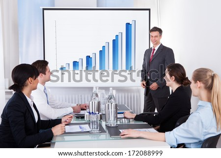 Mature Businessman Explaining Graph To His Colleagues Sitting In Office