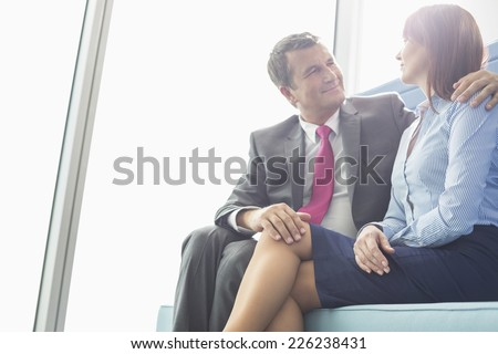 Mature businessman flirting with female colleague in office - stock photo