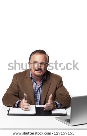 Mature businessman gesturing while working against white background