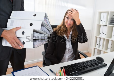 Mature Businessman Giving Pile Of Folders To Female Assistant In Office - stock photo